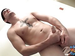 Inked naked thug plays with his giant dick and cums solo